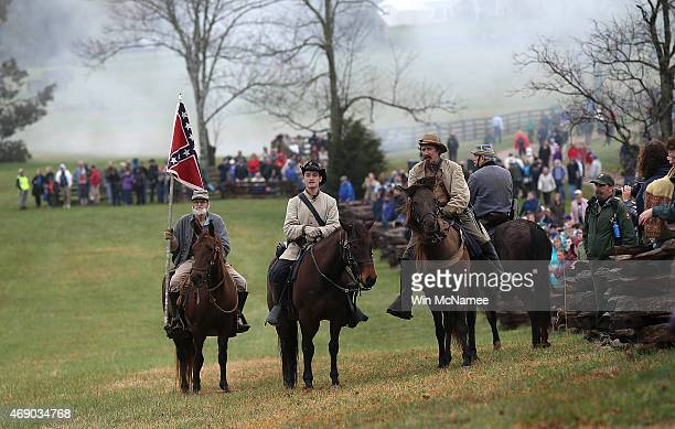 American Civil War reenactors dressed as Confederate cavalry take part in a reenactment of the Battle of Appomattox as spectators watch at the...