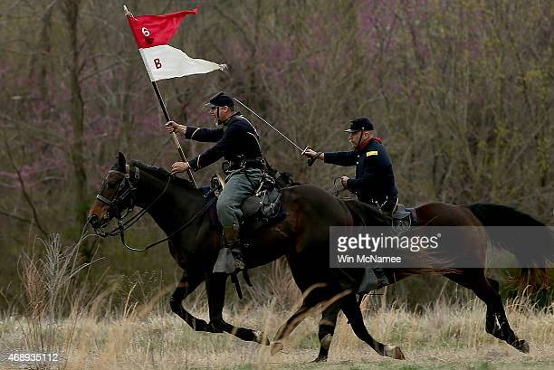 American Civil War reenactors dressed as Union cavalry charge Confederate troops at a reenactment of the Battle of Appomattox Station April 8 2015 in...