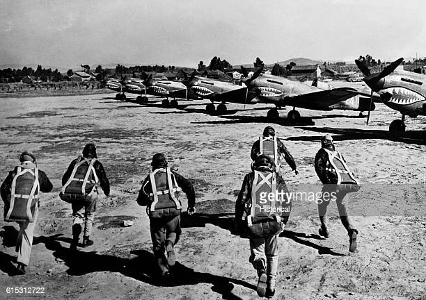 American civilian pilots of the American Volunteer Group, known as the Flying Tigers, run to their fighter planes at the sound of an air raid siren....