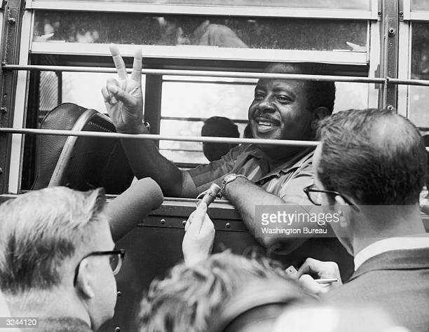 American clergyman and civil rights activist Ralph D Abernathy giving the peace sign as he sits in a police bus after being arrested for conducting...