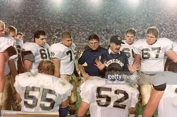 American college football coach Lou Holtz of Notre Dame guestures as the talks to his team on the sidelines in a packed stadium, late 1980s or early...