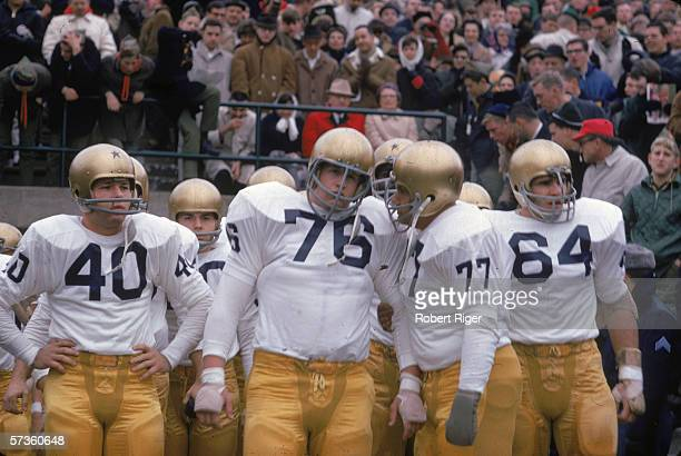 American college football players Tom O'Leary, Tom Regner, T. Alexander, and Pete Duranko of the Notre Dame Fighting Irish stand on the sidelines...