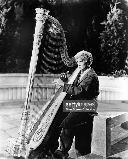 American comedian actor and harpist Harpo Marx playing a harp in 'Animal Crackers' directed by Victor Heerman 1930
