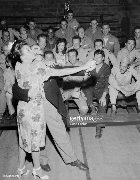 American comedian and actor Groucho Marx dances wth Dorothy Lamour at March Airforce Base for the amusement of the airmen on bleachers behinds them...