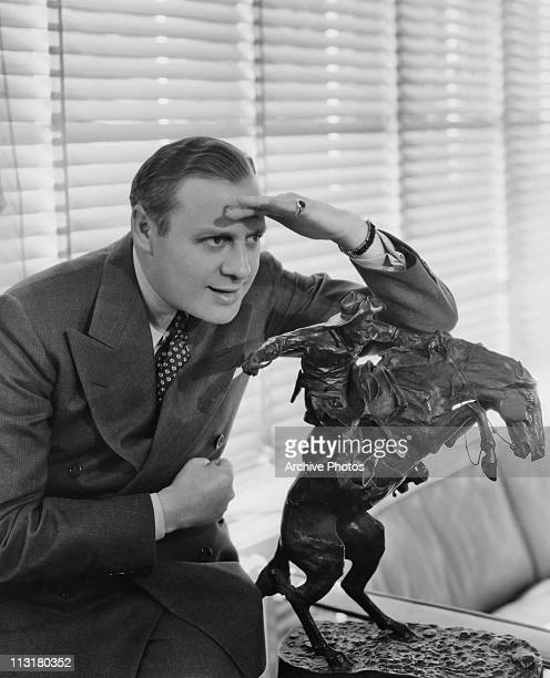 American comedian and actor Jack Benny shading his eyes as he looks over a statue in 1939