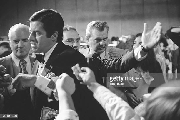 American comedian and actor Jerry Lewis walks among audience members who reach out and offer him money during his annual charity event to raise money...