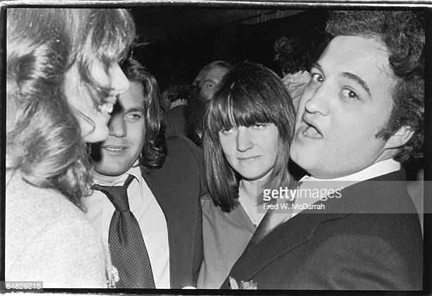 American comedian and actor John Belushi looks at the camera as he stands with his wife Judy Jacklin French actress and singer Jane Birkin and...