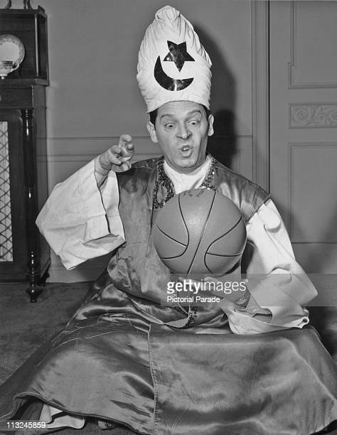 American comedian and actor Milton Berle pretending to cast a spell over a basketball in the 1940's.