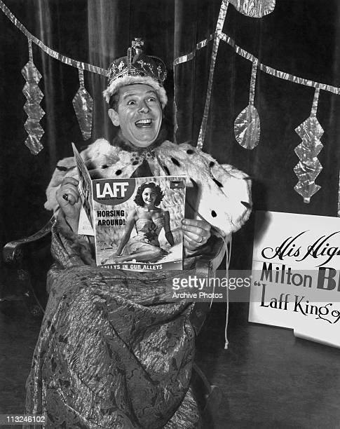 American comedian and actor Milton Berle wearing a king costume and holding a copy of Laff magazine with Ava Gardner on the cover circa 1946