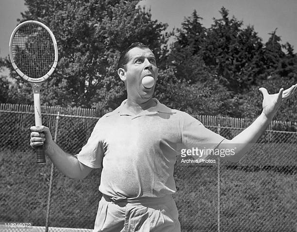 American comedian and actor Milton Berle with a tennis ball in his mouth while on holiday from his Texaco Star Theatre television show circa 1951.