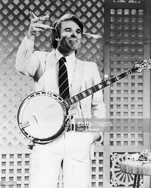 American comedian and actor Steve Martin gestures while wearing a gag arrow on his head and a banjo during a television appearance 1978