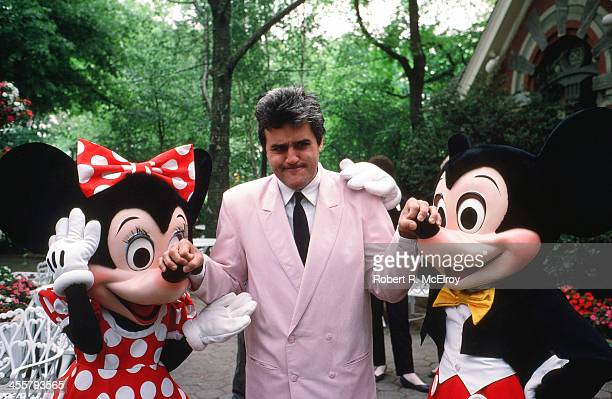 American comedian and television personality Jay Leno goofs around with Disney characters Minnie and Mickey Mouse at an unspecified event 1985