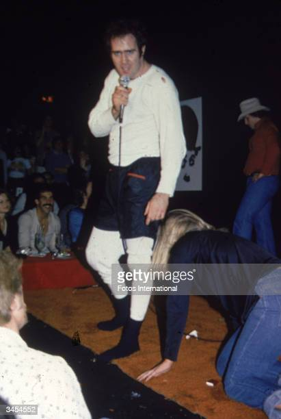 American comedian Andy Kaufman holds a microphone as a woman crawls toward him on stage during his female wrestling act at The Comedy Store nightclub...