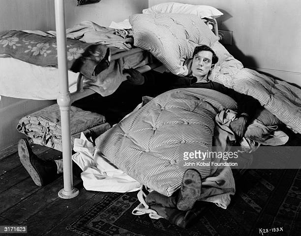 American comedian Buster Keaton lying on the floor under a collection of sheets and mattresses having fallen out of his bunk during a scene from his...