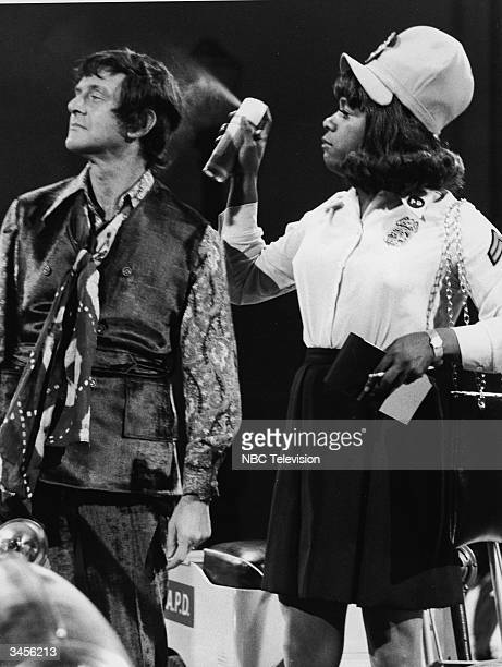 American comedian Flip Wilson in drag costume as a meter maid sprays hairspray on guest Tony Randall's hair in a still from the TV comedy series 'The...