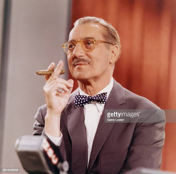 American comedian Groucho Marx holds a cigar as he hosts an episode of the television show 'You Bet Your Life' 1950s or 1960s