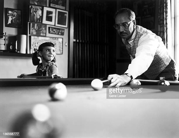 American comedian Groucho Marx playing pool with his daughter Melinda 5th January 1954