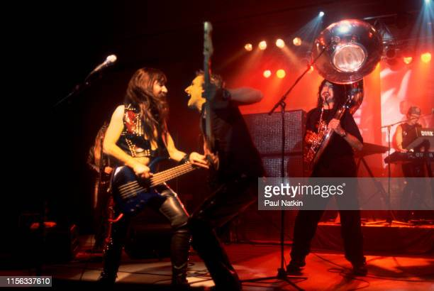 American comedian Harry Shearer in costume as British musician Derek Smalls of the group Spinal Tap plays bass guitar with several unidentified guest...