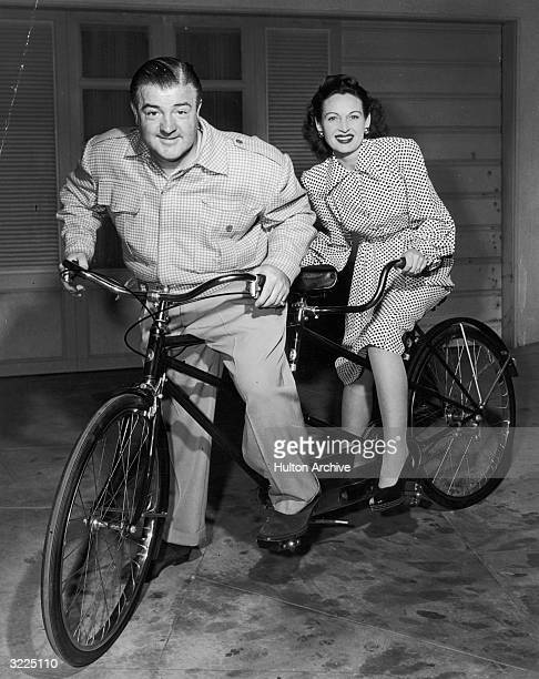 American comedian Lou Costello poses with his wife Anne Battlers on a tandem bicycle They each stand with one foot on the pedals