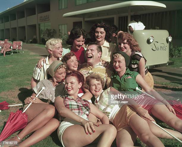 American comedian Milton Berle rolls his eyes and laughs as he sits on the grass at the Sands Hotel surrounded by the women of the Sands chorus line...
