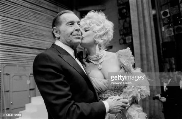 American comedian Milton Berle smiles as actress Ann Jillian kisses his cheek during 'The Parade of Stars' a benefit event for the Actor's Fund New...