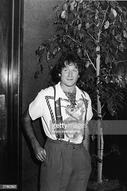 American comedian Robin Williams of the television series 'Mork And Mindy' attends an ABC stars luncheon wearing a dragon print shirt and striped...
