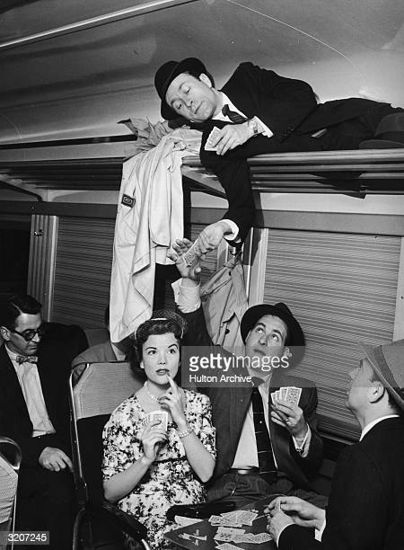 American comedian Sid Caesar receives some playing cards from actor Howard Morris lying in a luggage rack during a card game with actors Nanette...