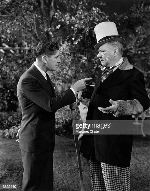 American comedian W C Fields jokes with director A Edward Sutherland during production of the Paramount film 'Poppy'