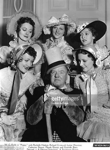 American comedian W C Fields surrounded by society beauties in a scene from the film 'Poppy' directed by A Edward Sutherland for Paramount