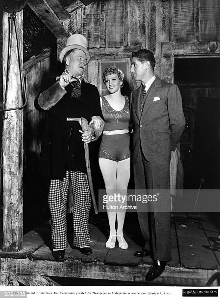 American comedian WC Fields chats with Ruby Wood the circus aerialist and director A Edward Sutherland on the carnival set of the Paramount film...