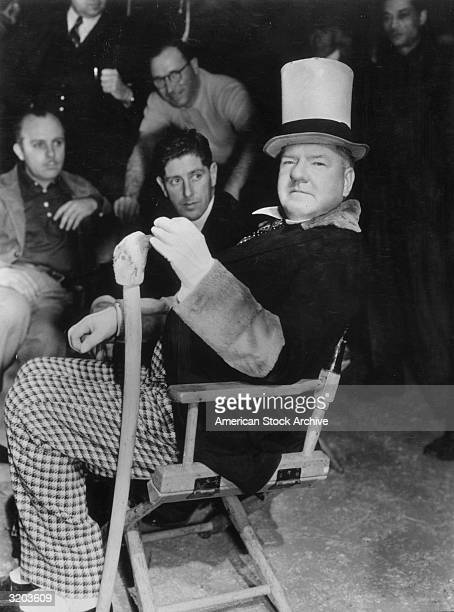 American comedian WC Fields holds a wooden cane while sitting in a folding chair in front of crewmembers on the set of director A Edward Sutherland's...