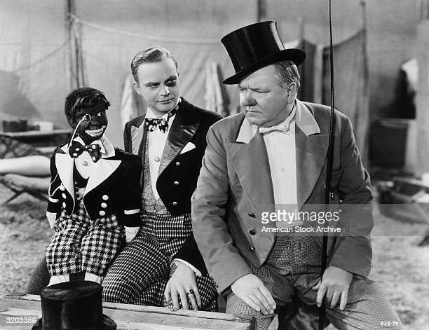 American comedian WC Fields sits with American ventriloquist Edgar Bergen and his dummy Charlie McCarthy who wears blackface makeup in a still from...
