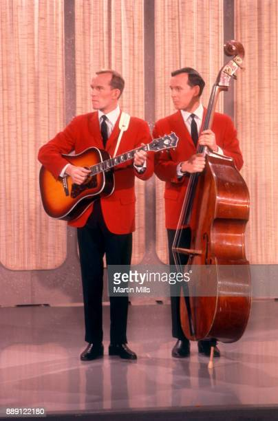 American comedians composers and musicians Tom Smothers plays the guitar and his brother Dick Smothers plays the cello during a televison show circa...