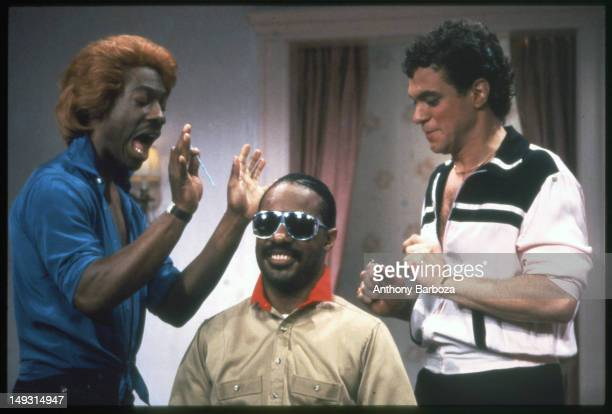 American comedians Eddie Murphy in costume as the character Dion and Joe Piscopo in costume as the character Blaine perform a skit with musician...