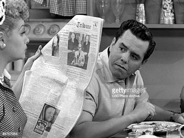 American comedienne and actress Lucille Ball , as Lucy Ricardo, reads a page from a newspaper while Cuban-born American actor and musician Desi Arnaz...