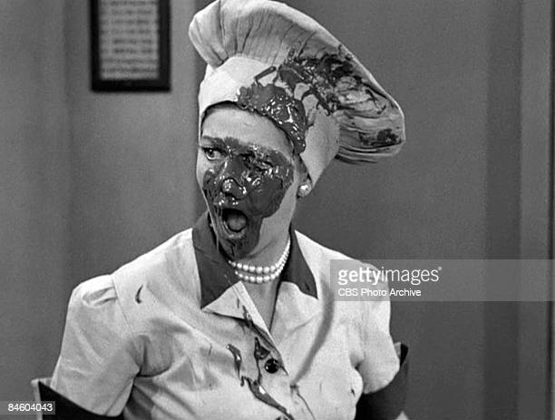 American comedienne and actress Lucille Ball , as Lucy Ricardo with a face covered in chocolate, works in a candy factory in an episode of the...