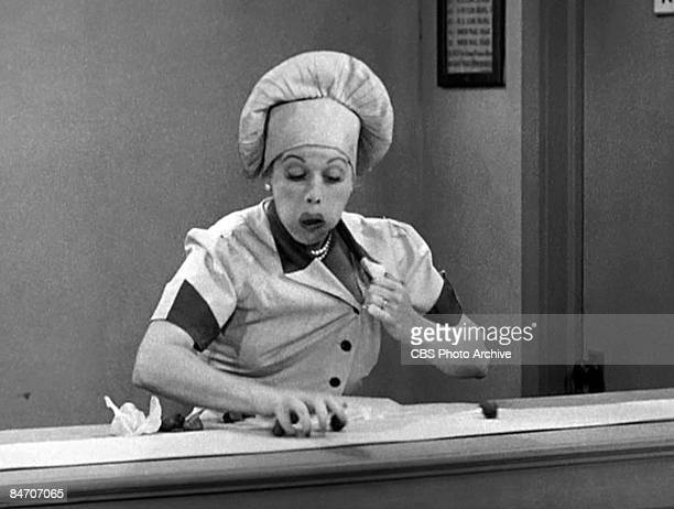 American comedienne and actress Lucille Ball , as Lucy Ricardo, work at a candy factory conveyor belt on an episode of the television comedy 'I Love...