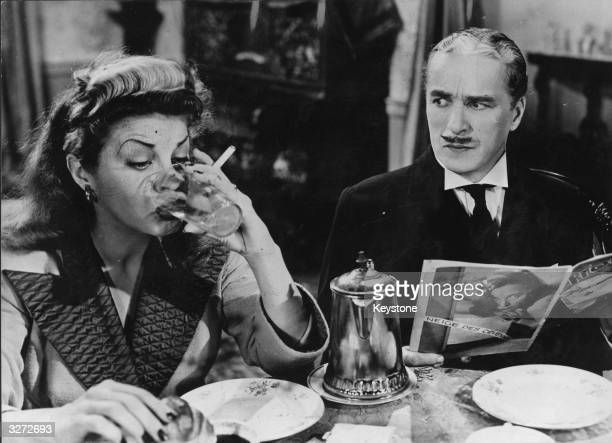American comedienne and vocalist Martha Raye drains her glass unaware of the disgust felt by the fastidious Henri Verdoux in a scene from the crime...