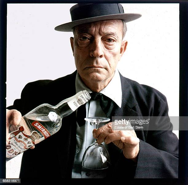 American comic actor and filmmaker Buster Keaton (1895 - 1966) about to pour a drink onto an upturned glass , 1957. From an advertising shoot for Smirnoff vodka.