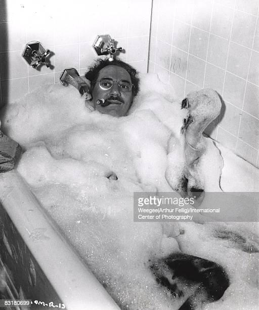 American comic actor and performer Groucho Marx in a bath tub with lots of soapy bubbles fully clothed smoking a cigar New York 1952 Photo by...