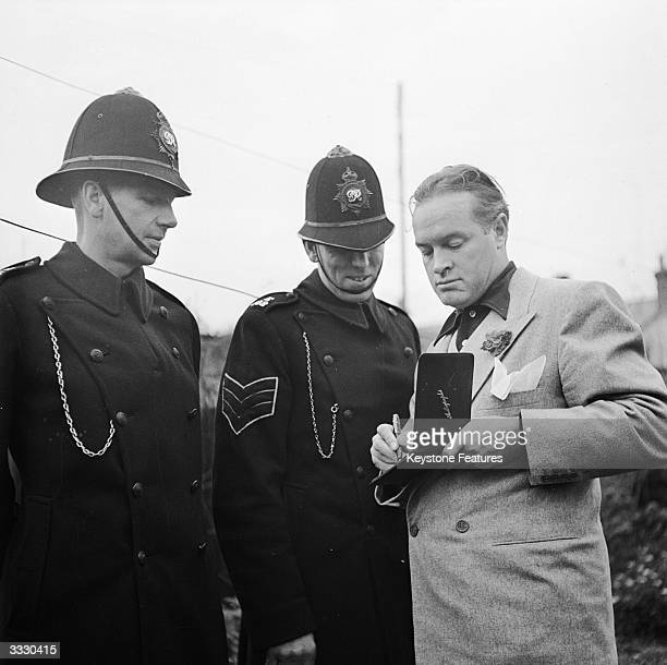American comic actor Bob Hope signs autographs for the local police sergeant and constable during the star's trip to visit family in Hitchin,...