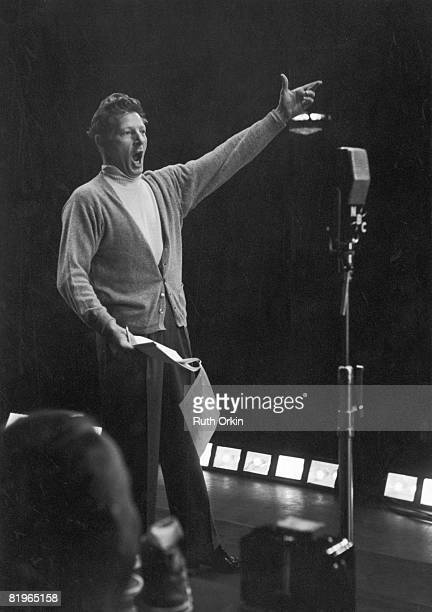 American comic actor Danny Kaye gestures expansively as he sings into a WNBC radio microphone New York late 1940s or early 1950s