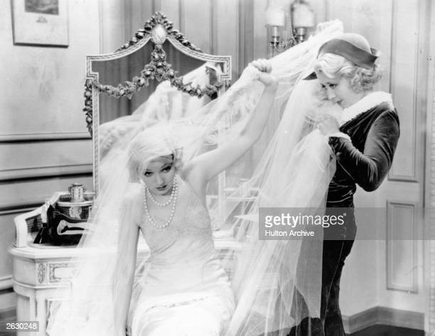 American comic actress Joan Blondell struggles with the cumbersome veil of a wedding dress in a scene from an unknown film