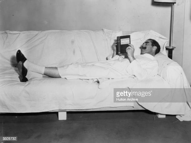 American comic Groucho Marx reading 'Principals of Education' during a break in the filming of 'Duck Soup'