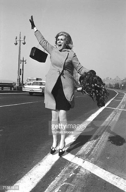 American commedienne and entertainer Joan Rivers jumps into the air her purse over an outstretched arm and a wig in her other hand as she tries to...