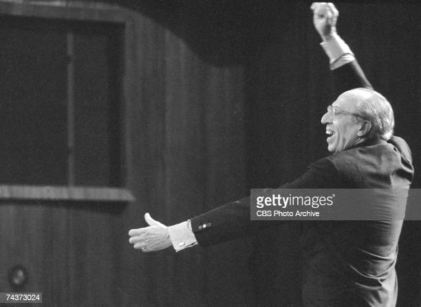 American composer and conductor Aaron Copland smiles as he conducts during the filming of one of his televised 'Young People's Concerts' featuring...