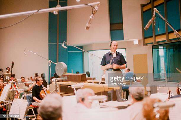American composer and conductor Henry Mancini smiles as he stands before musicians in a studio 1988
