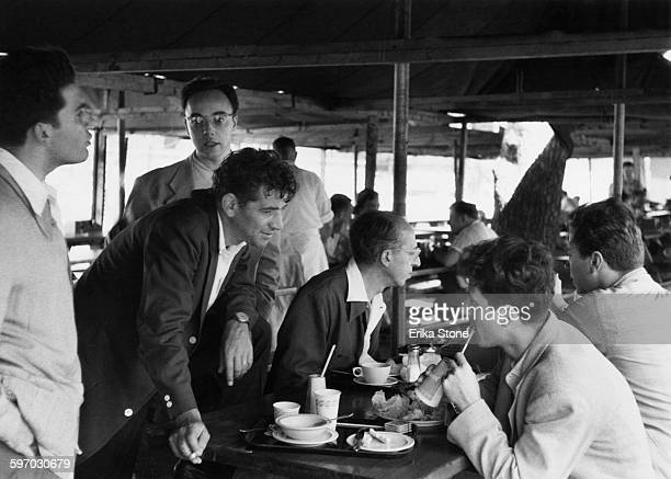 American composer and conductor Leonard Bernstein at lunch with fellow composers Aaron Copland and Lukas Foss and pianist and teacher Seymour Lipkin...