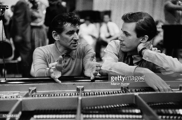 American composer and conductor Leonard Bernstein in conversation with Canadian pianist Glenn Gould at a piano at a Columbia Records recording studio...