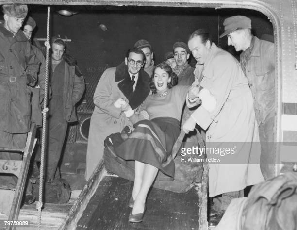 American composer Irving Berlin and Britishborn American comedian Bob Hope help American actress Jinx Falkenburg to slide down a cargo ramp from her...